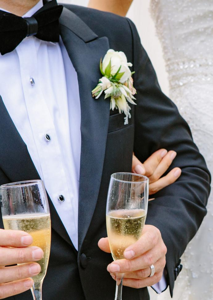 a groom holding two glasses of champagne