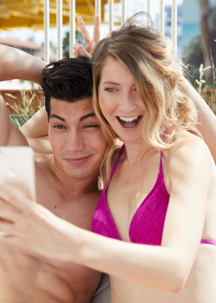 a man and woman in bathing suits taking a selfie