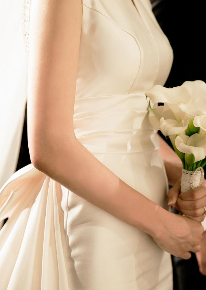 a woman in a bridal gown holding a bouquet