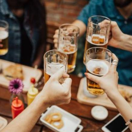 Four hands clinking mugs of beer over a wooden table