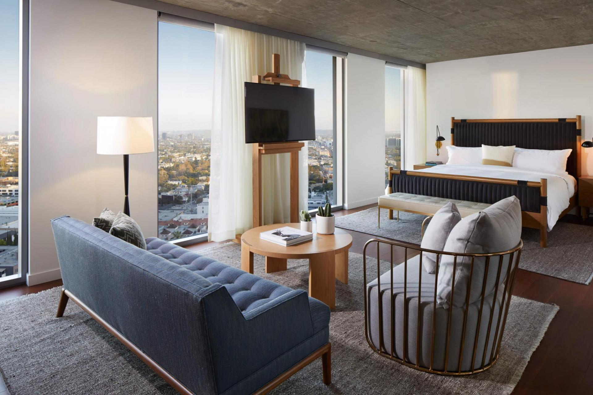 A modern living area and bed in a Jeremy West Hollywood Hotel suite