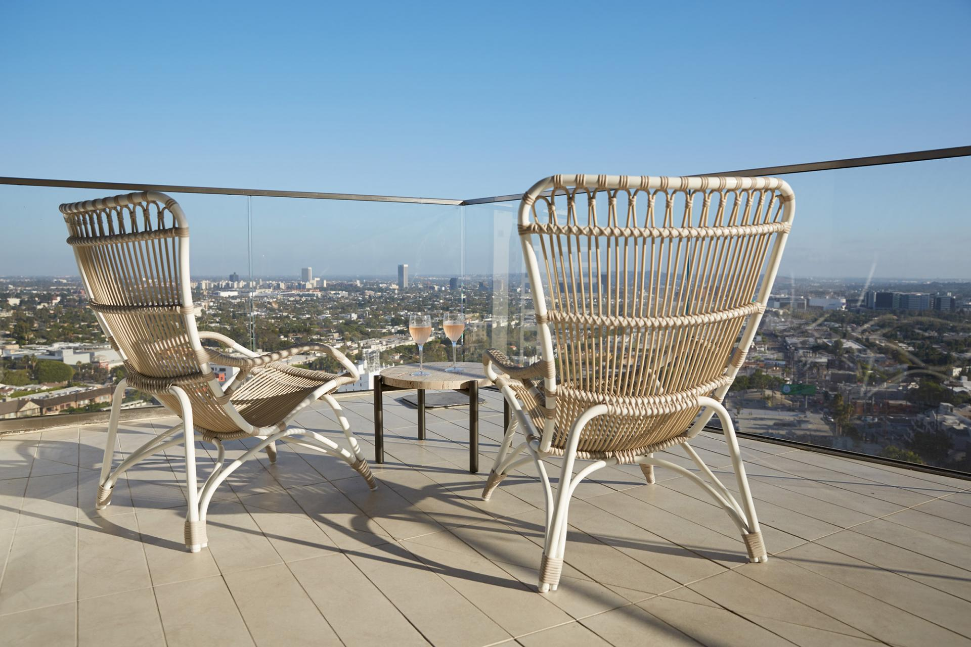 Two wicker chairs on a rooftop patio overlooking West Hollywood
