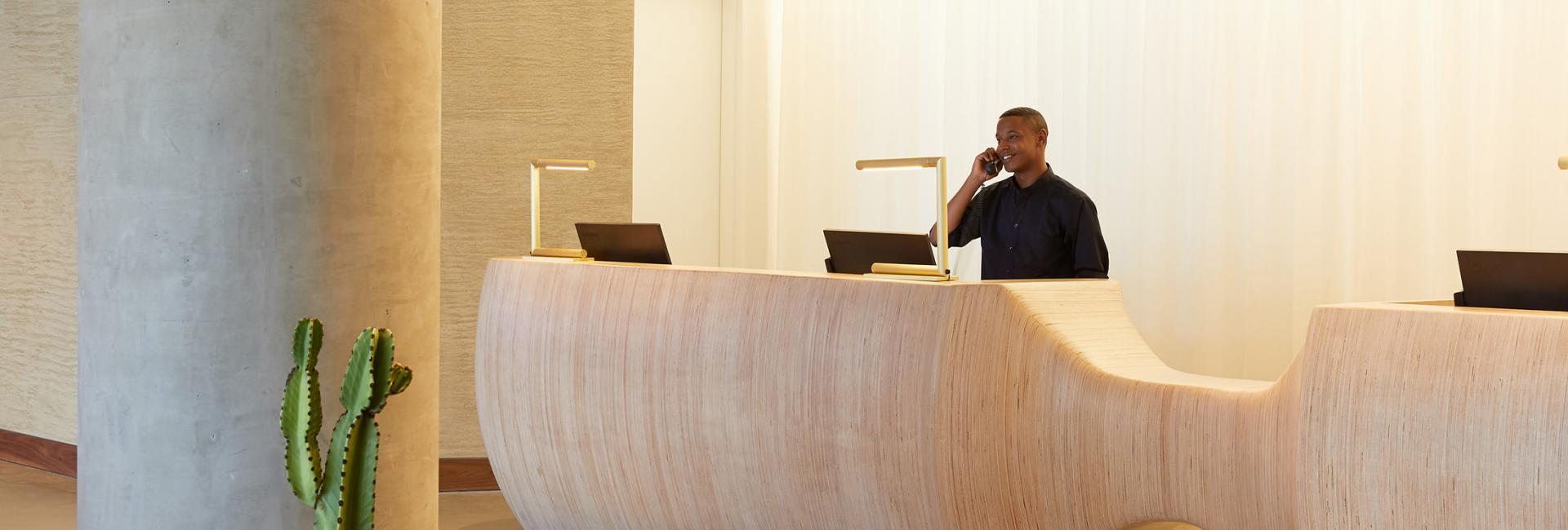 A man talking on the phone at a hotel front desk