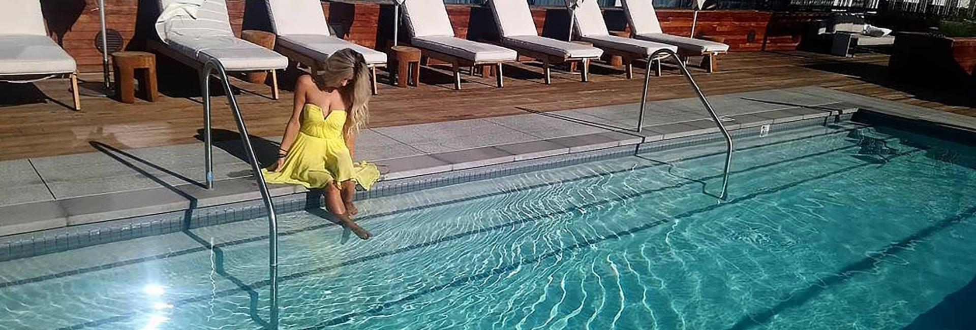 woman dangling her feed in the pool
