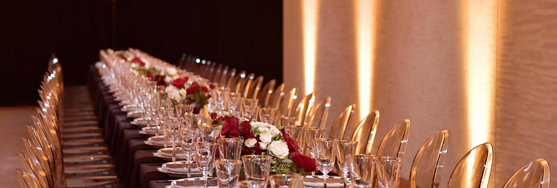 A long table set with pink and gold plates and glassware