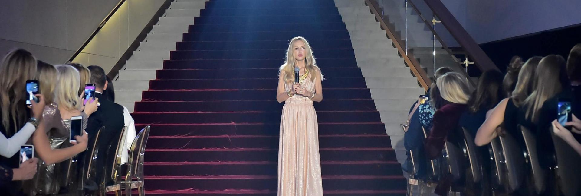 A woman in a long pink gown standing in front of a large staircase