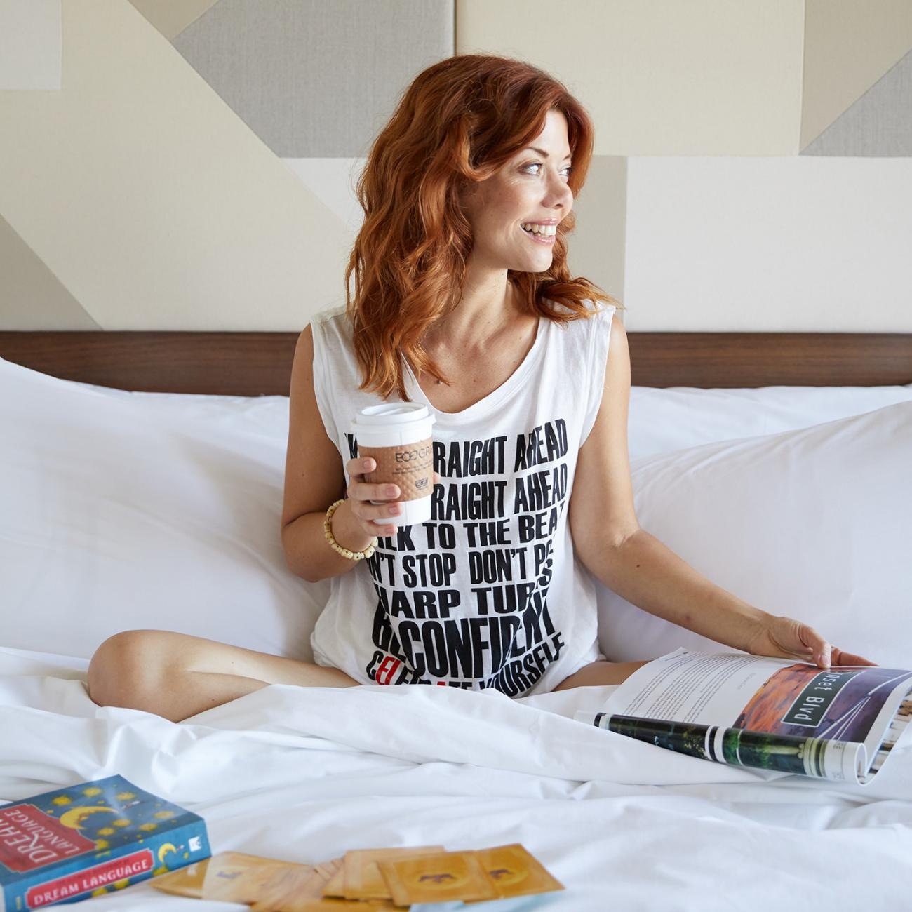 A woman hanging out in bed reading books and drinking coffee