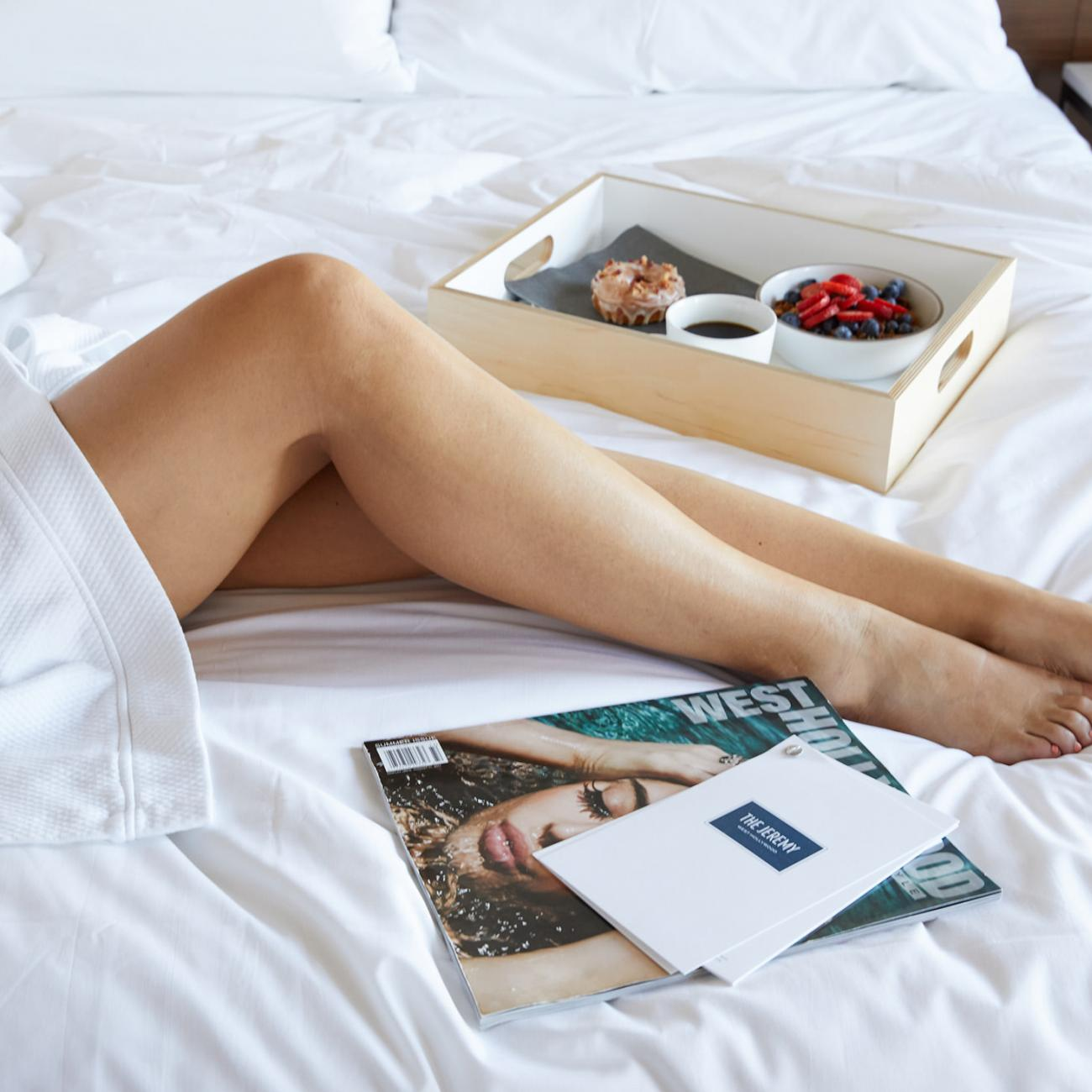 A woman in a bathrobe having breakfast in bed