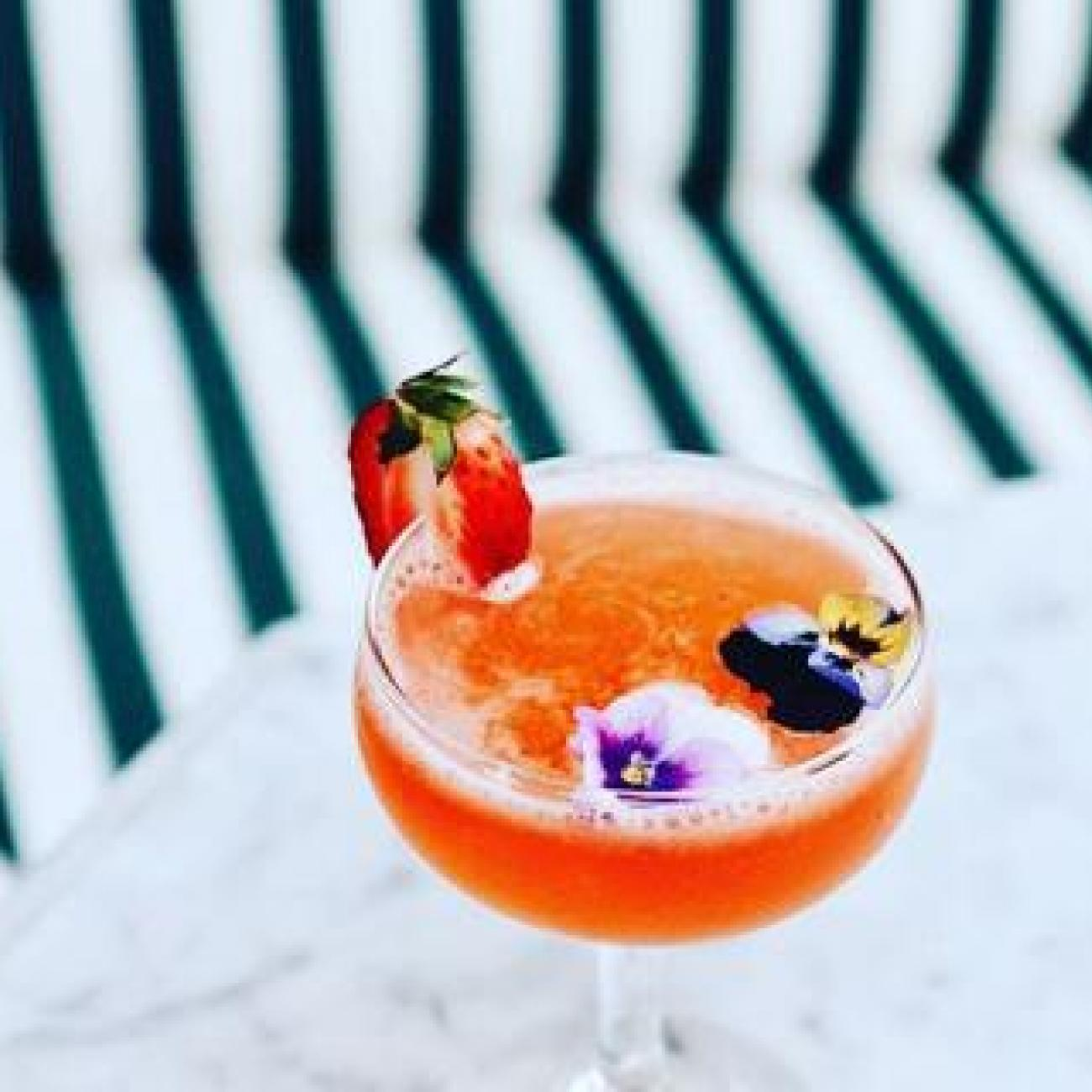 A frothy orange cocktail garnished with strawberry and flowers